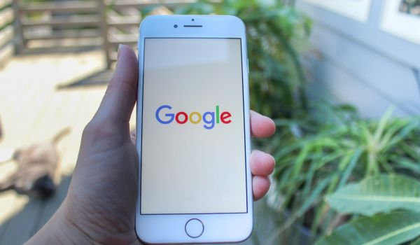 A hand holding a phone showing the Google logo