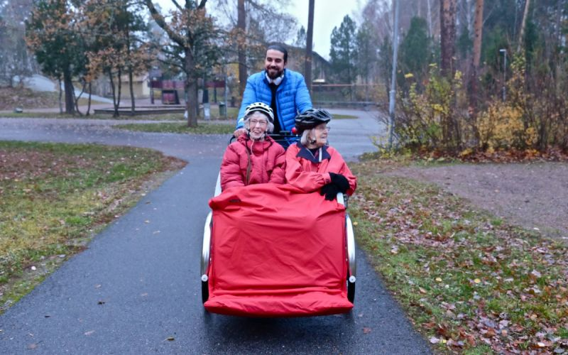 A volunteer taking two senior citizens on a bike ride through the forest in Sweden.