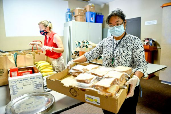 woman with box of sandwiches at food bank