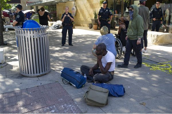 homeless man sitting near city hall as police watch the area