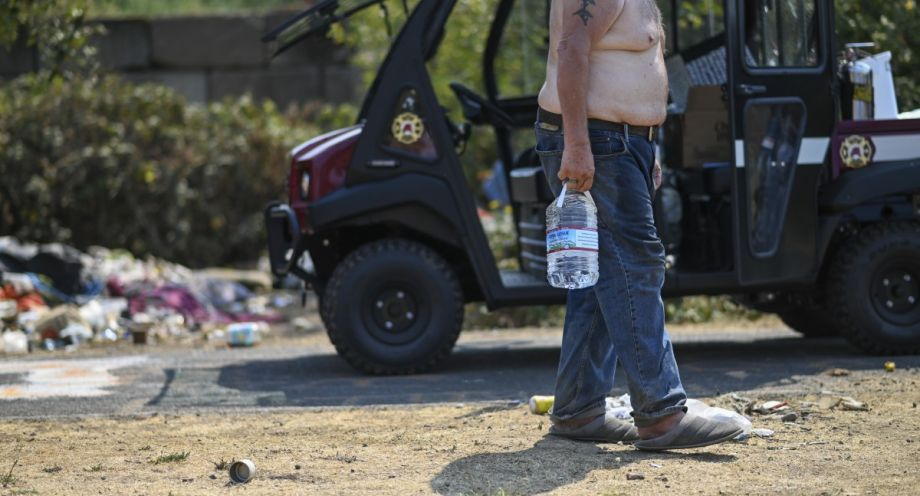 Man carrying water to his campsite during a heat wave