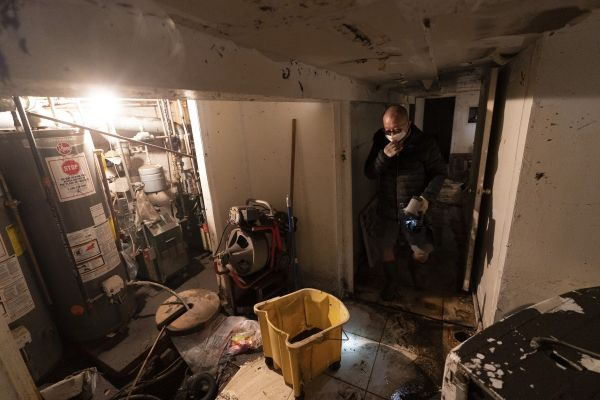 A man who gave his name as John helps to clean a friend's basement, Friday, Sept. 3, 2021, in Queens, New York. The area was flooded Wednesday as rain from the remnants of Hurricane Ida sent the New York City area into a state of emergency.