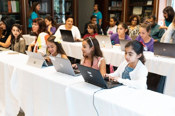 Girls using computers in a Code/Art session to teach coding and STEM skills