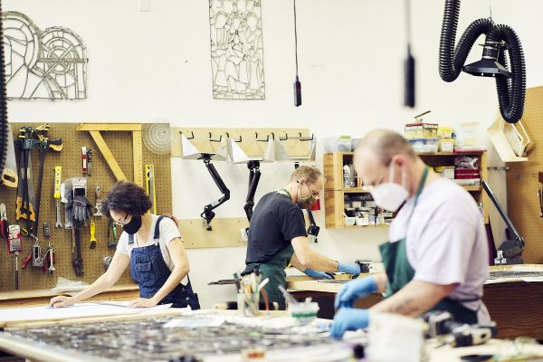 Three workers creating art at the stained glass studio