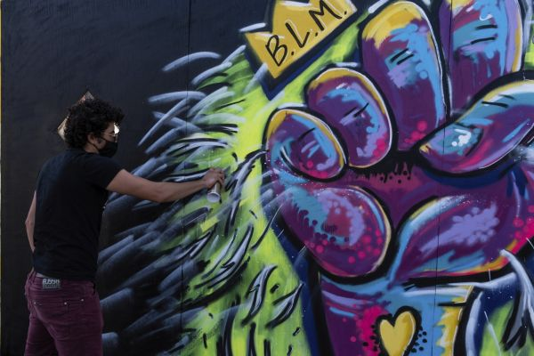 A person spray-painting a BLM mural