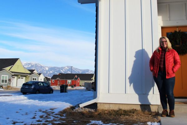 Woman standing in front of Montana home with a mountain view